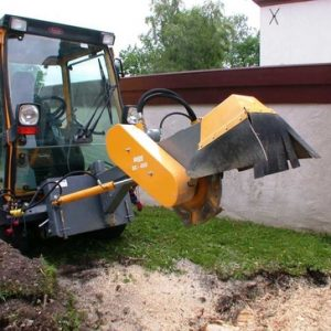 Picture of an employee using heavy machinery to grind and remove a stump in the back yard of a home in Canton, OH.